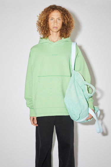 Acne Studios mint green oversized hooded sweatshirt is made of cotton and features an Acne Studios logo on the front.