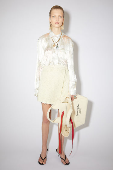 Acne Studios cream beige casual skirt is made of a cotton blend with an asymmetric button closure.
