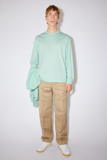 Acne Studios spearmint green long sleeve t-shirt is made of organic cotton with a face logo patch and ribbed details.