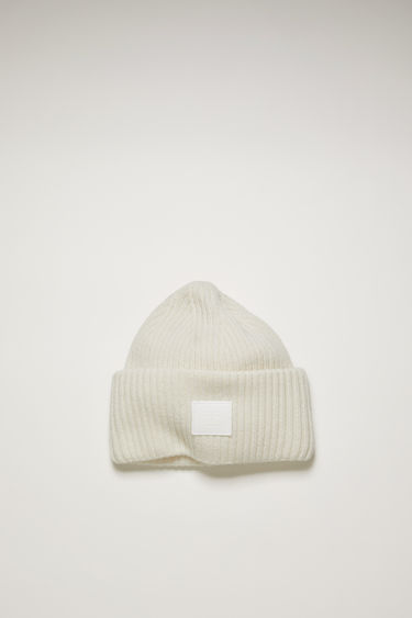 Acne Studios optic white beanie is knitted in a thick rib-stitch from soft wool and features a tonal face-embroidered patch on the turn-up.