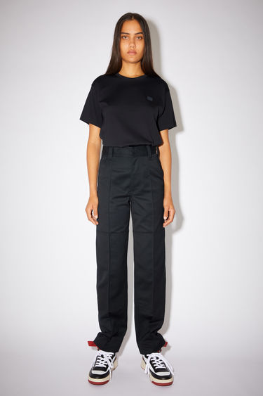 Acne Studios black classic workwear trousers are made of a cotton twill blend with creased legs and a leather face patch.