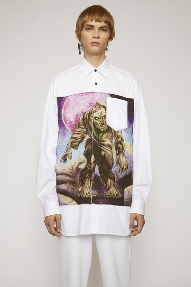 Acne Studios launches an exclusive range with Monster in My PocketⓇ. This optic white shirt is cut from cotton poplin with a chest pocket and has a large scale patch at the back, featuring a zombie motif.