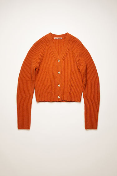Acne Studios pumpkin orange cardigan is knitted from wool in a chunky ribbed pattern. It's accented with a fully fashioned v-neck, shoulders and rounded sleeves to define the waist.