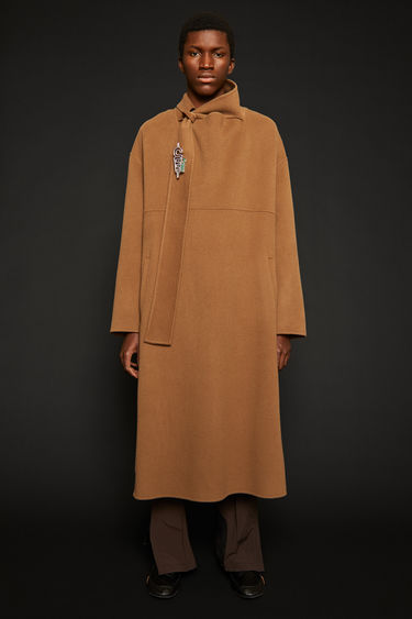 Acne Studios light camel poncho is crafted to an oversized silhouette from double-face wool and features a scarf-collar and a concealed button placket that runs down the side seams and sleeves.
