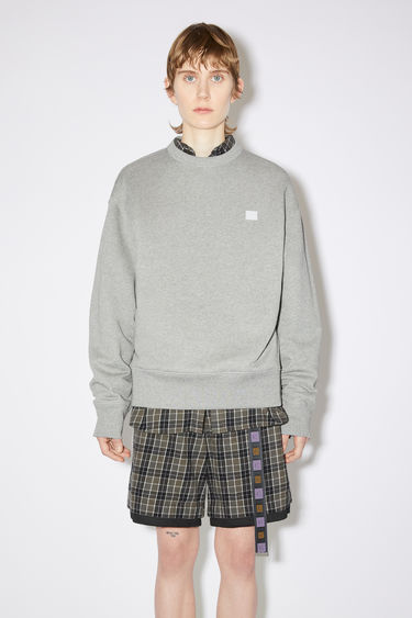 Acne Studios light grey melange oversized crew neck sweatshirt is made of organic cotton with a face patch and ribbed details.