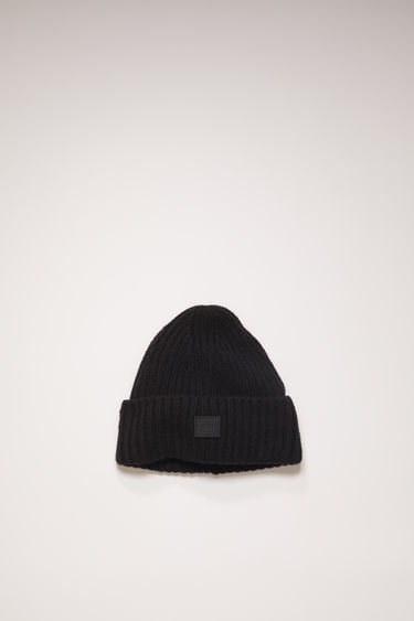 Acne Studios Mini Pansy N Face black beanie is rib-knitted from soft wool and detailed with a face-embroidered patch on the turn-up brim.