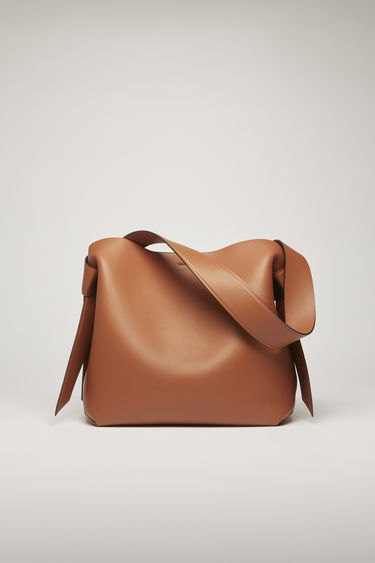 Acne Studios Musubi Midi almond brown bag features twisted knots inspired by the formation of traditional Japanese obi sash. It's crafted from soft grain leather and has a central zipped divider to store small essentials.