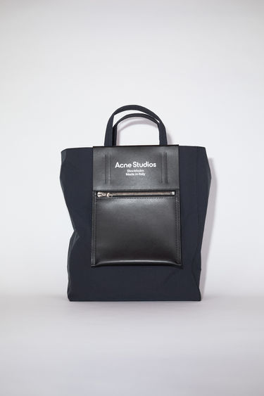 Acne Studios Baker Out black/black bag is made from durable nylon with a papery texture and crafted in a boxy shape. It features a leather zipped pocket with a white printed logo on the front.