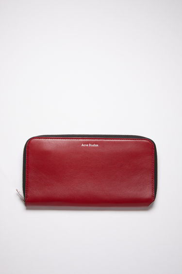 Acne Studios burgundy multi continental wallet is made of smooth leather with 12 card slots, two bill sleeves, and a zippered compartment for coins.