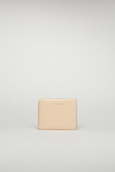 Acne Studios blush pink trifold wallet is crafted from high-shine leather and completed with four card slots, a note compartment and a coin pocket.