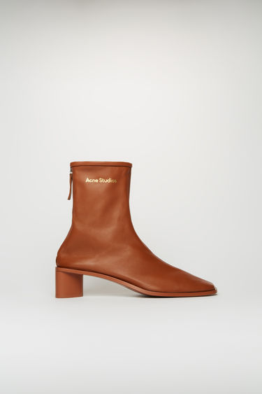 Acne Studios rust brown/rust brown boots are crafted from soft grained leather to a snug sock-like fit and set on a tonal block heel. They're secured with a metal zip and accented gold stamped logo on the ankle.