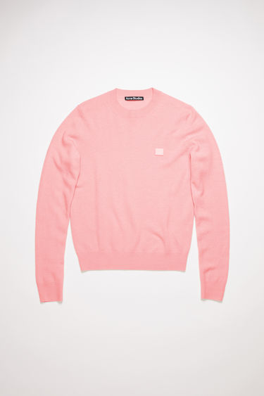 Acne Studios blush pink crew neck sweater is made from wool with a face logo patch and ribbed details.
