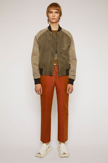 Acne Studios khaki green bomber jacket is crafted from supple suede and features washed out printed twill sleeves and contrasting ribbed trims.