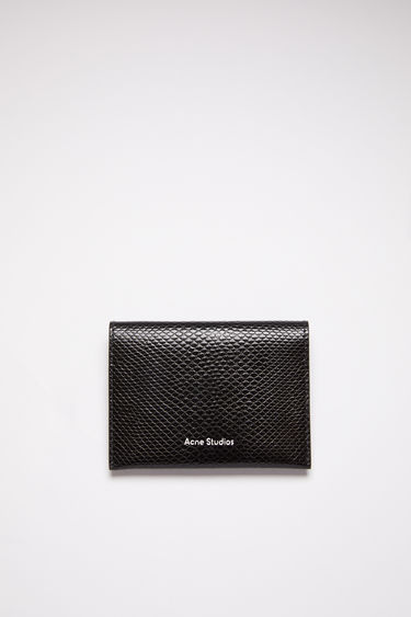 Acne Studios black bifold card holder is made of calf leather with four card slots and a silver stamped logo on the front.