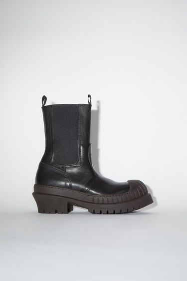 Acne Studios black/dark brown leather boots present a refined update to the classic Chelsea silhouette. It's crafted from to a rounded shape that's reinforced with a rubber toe cap and set on a chunky treaded sole.