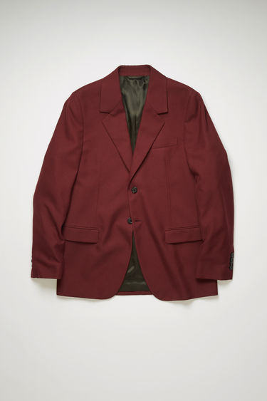 Acne Studios burgundy suit jacket is tailored to a single-breasted silhouette with stitched darts through the waist and has notch lapels and lightly padded shoulders.