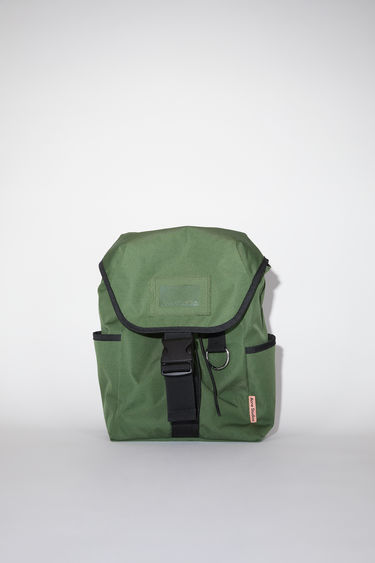 Acne Studios dark green durable backpack has a clear vinyl ID pocket, two generous side pockets, adjustable straps, and an Acne Studios logo tab.
