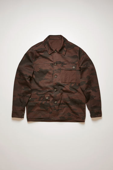Acne Studios mahogany brownreversible chore jacket is cut from garment-dyed cotton that has a camouflage print on one side and solid tone on the other. It's crafted with a point collar, buttoned flap pockets and five-button closure.