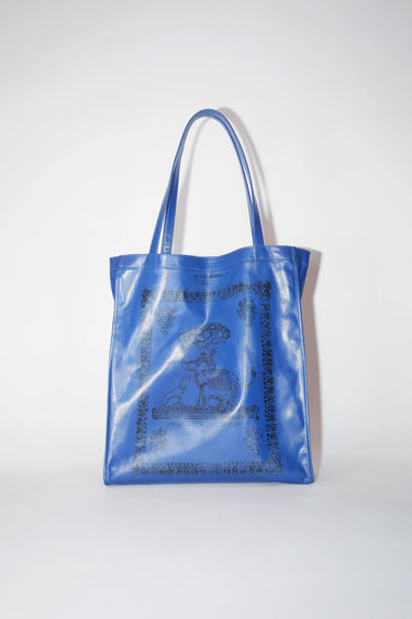 Acne Studios denim blue oilcloth tote bag features Acne Studios branding.
