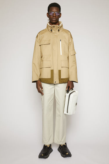 Acne Studios mushroom beige/taupe grey field jacket is crafted from technical cotton twill and is equipped with four flap pockets and a packaway hood.