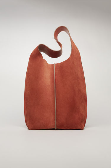 Acne Studios rust orange tote bag is crafted from supple suede and has a silver-tone metal clasp which opens to reveal a spacious logo-embossed leather lining with a detachable zip pouch.