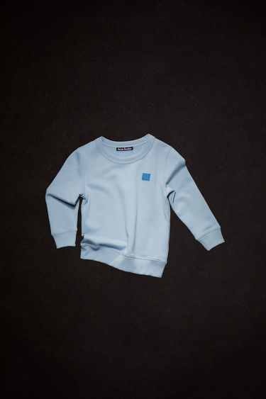 Acne Studios powder blue crew neck sweatshirt is made of organic cotton with a face patch and ribbed details.