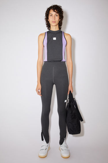 Acne Studios black running trousers are made of lightweight jersey with a reflective face logo on the front thigh.