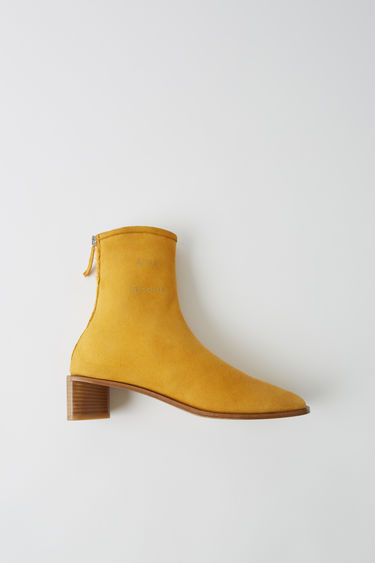 Acne Studios yellow/beige suede ankle boots are lined with lamb shearling and set on a triangular block heel.