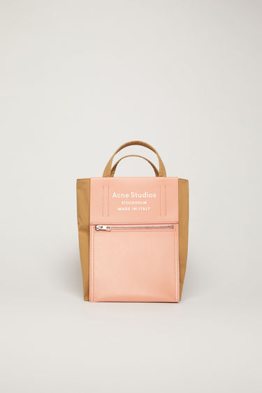 Acne Studios Baker Out S brown/pink is a small tote bag with an embossed logo pocket placed outside of the bag.