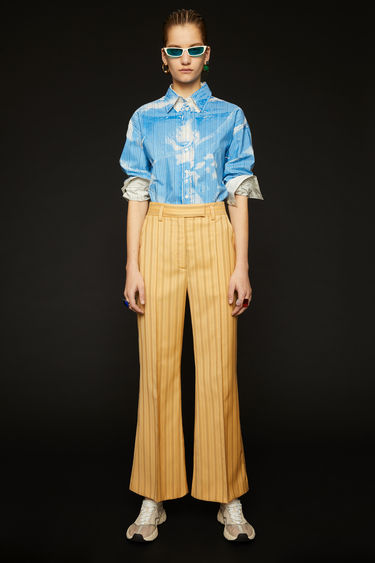 Acne Studios pale orange pinstripe trousers are crafted from wool and are cut to fit slim through the hips before falling into kick-flare legs.