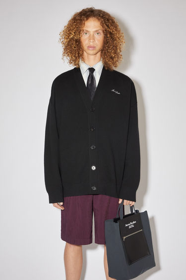 Acne Studios black v-neck cardigan sweater is a double face knitwear in wool and cotton with an embroidered logo at the chest.