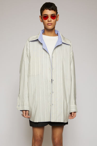 Acne Studios reversible overshirt is crafted from cotton with light padding and displays pinstripes on one side, and solid powder blue when reversed.