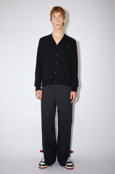 Acne Studios black v-neck cardigan sweater is made from wool with a face logo patch and ribbed details.