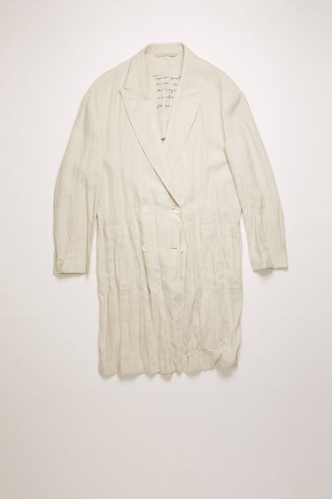 Acne Studios white melange double-breasted coat is crafted from creased linen with peak lapels and two patch pockets and features an embroidered care instruction label at back neck.