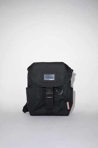 Acne Studios black durable backpack has a clear vinyl ID pocket, two generous side pockets, adjustable straps, and an Acne Studios logo tab.