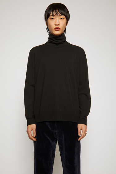 Acne Studios black sweater is knitted from soft wool-blend yarn to a relaxed fit with a roll neck and framed with ribbed edges.