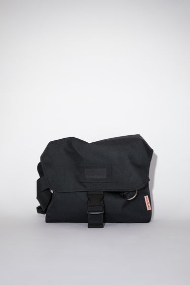 Acne Studios black large, durable messenger bag has a clear vinyl ID pocket, strap with decorative stitching, and an Acne Studios logo tab.