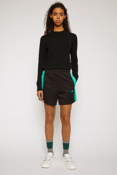 Acne Studios black track shorts are are crafted from lustrous technical jersey with an elasticated waist and accented with a face-embroidered patch and contrasting side-stripes.