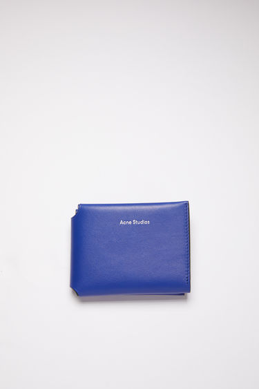Acne Studios blue multi colour block trifold card wallet is made of soft grained leather with a coin pocket, bill sleeve, and four card slots, featuring a silver stamped logo on the front.