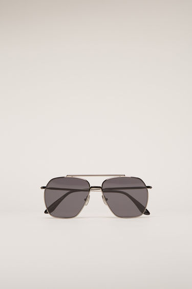 Acne Studios Anteom dark silver/black sunglasses are shaped with squared aviator frames that are set with black tinted lenses and then finished with acetate arm tips.