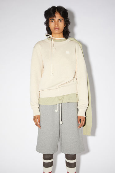 Acne Studios oatmeal melange regular fit crew neck sweatshirt features ribbed details and a face patch on the front.