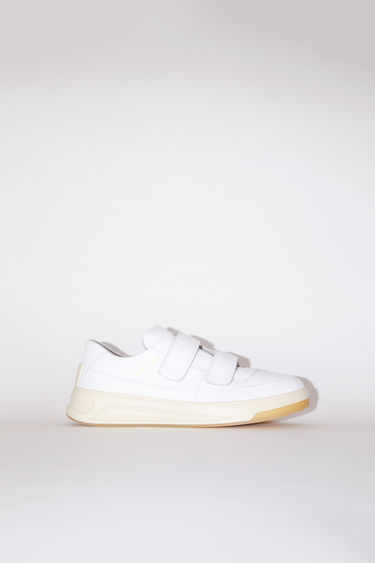 Acne Studios white take design cues from 80s tennis shoes. They're made of calf leather with a low top silhouette and embossed with a gold logo on the side.