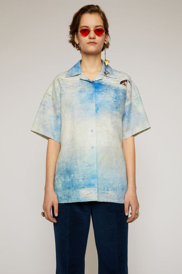 Acne Studios blue/white shirt features a painting of Swedish nature by August Strindberg. It's crafted from linen and cut to a boxy fit with a open collar and short sleeves.