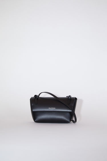 Acne Studios black flap purse features twisted knots inspired by traditional Japanese obi sashes.