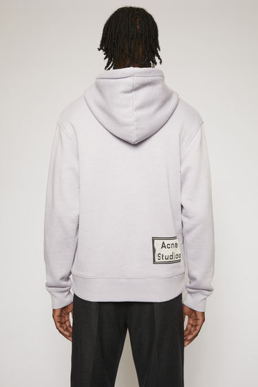 Acne Studios lilac purple hooded sweatshirt is crafted from loopback jersey with and features a reversed label patch at the lower back.