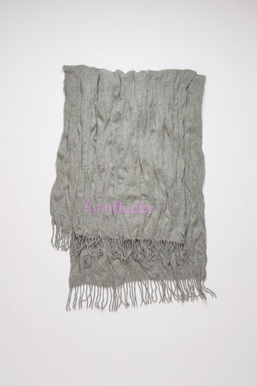 Acne Studios light grey melange scarf is crafted to a wide dimension from wool with crinkle effect and features a jacquard logo above the fringed edges.