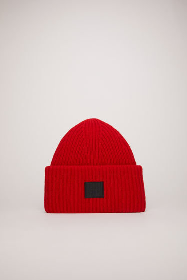 Acne Studios red/black beanie is rib-knitted from soft wool and accented with a face-embroidered patch on the front.