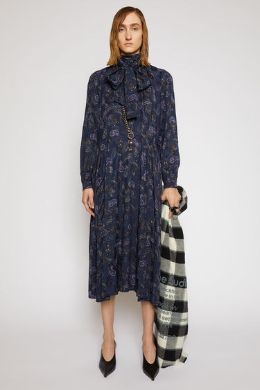 Acne Studios black/purple dress is crafted from lightweight viscose that's printed with paisley motifs. It's cut to a fluid drape with a tie at the neck and finished with a gathered waist seam.